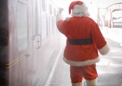 Santa ringing the bell for passengers to board the Santa Express train